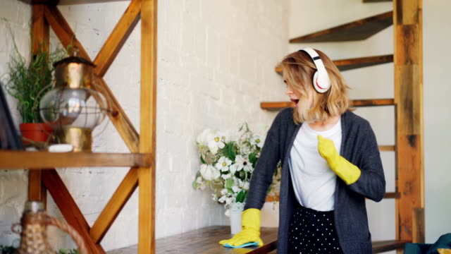 joyful woman is listening to music with headphones, dancing and singing during everyday housework. girl is dusting table holding cloth and wearing gloves. - stay at home parent stock videos & royalty-free footage