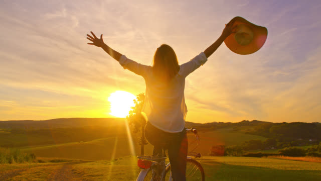 vídeos de stock e filmes b-roll de slo mo joyful woman outstretching her arms on the top of a hill - liberdade