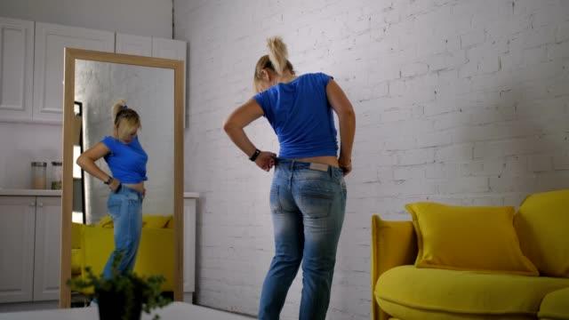 glada kvinna visar hennes vikt förlust prestation - byxor bildbanksvideor och videomaterial från bakom kulisserna