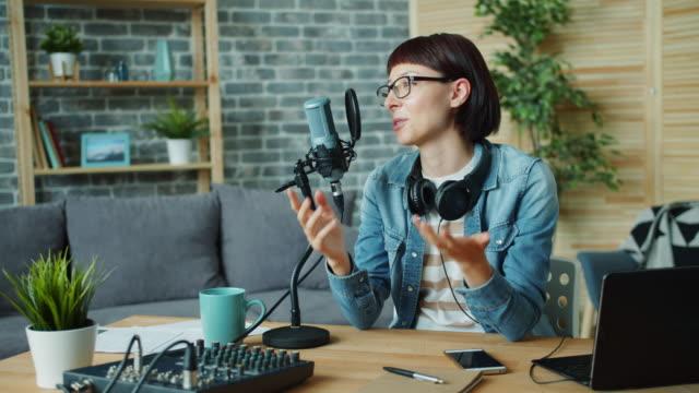 vídeos de stock, filmes e b-roll de mulher alegre que fala no microfone que ri gesticulando no estúdio de gravação - podcast