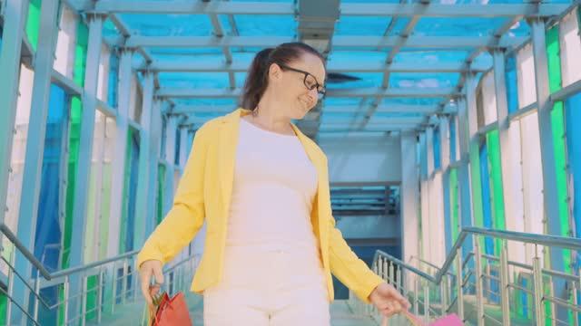 vídeos y material grabado en eventos de stock de mujer alegre con compras baja escaleras - black friday sale
