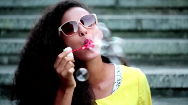 vídeos de stock, filmes e b-roll de alegre mulher com bolhas de sabão - clipe