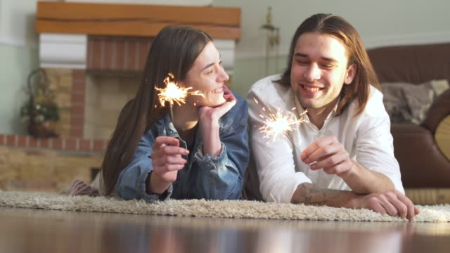 Joyful young beautiful guy and girl with sparklers in hands lying on the carpet at home