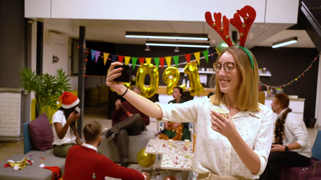 vídeos de stock, filmes e b-roll de alegre jovem empreendedora moderna tirando uma selfie durante festa de escritório enquanto usava chifres de renas fantasia - feriado evento