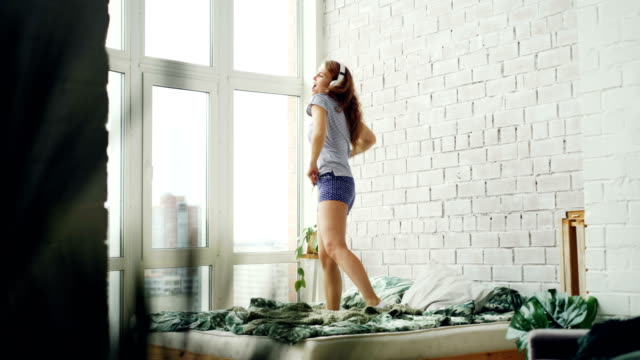Joyful young woman is dancing on bed at home wearing headphones and enjoying music. Double bed, brick wall, panoramic window and green plant are visible.