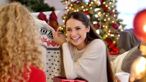 vidéos et rushes de joyeuse jeune femme ouvre un cadeau de noël pendant laid échange de cadeaux de pull de noël - cadeau