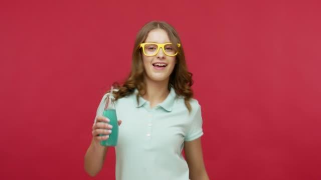 vídeos y material grabado en eventos de stock de joven alegre con gafas brillantes sosteniendo cóctel azul y bailando, bebiendo alcohol en la fiesta - chica adolescente