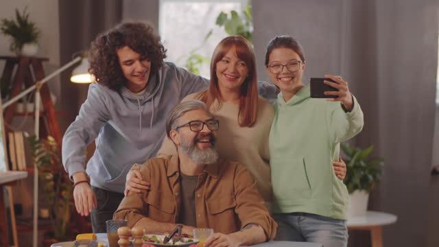 夕食時にスマートフォンで自分撮りをする喜びの家族 - 兄弟姉妹点の映像素材/bロール