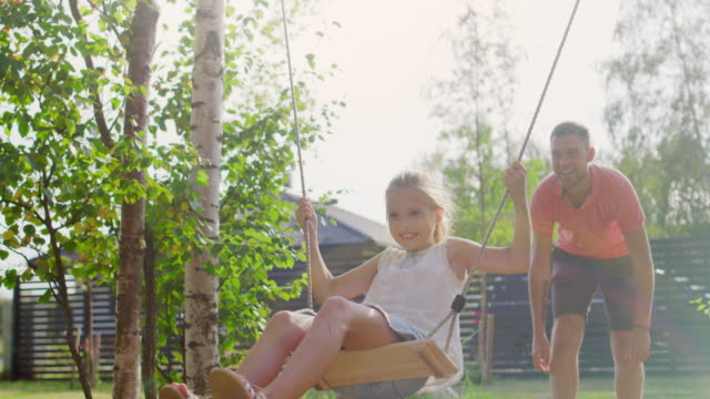 joyous father pushes swings with his cute little daughter on them . happy family spends time together one sunny summer day in the idyllics backyard. - задний или передний двор стоковые видео и кадры b-roll