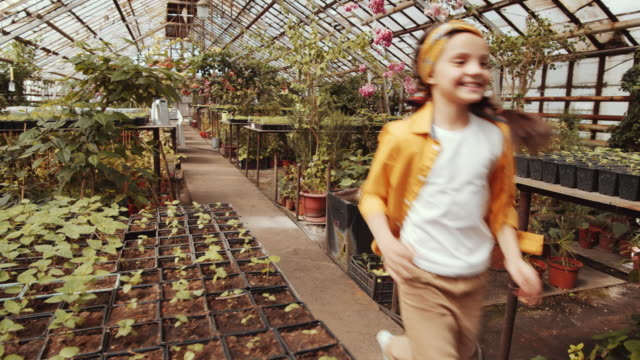 joyous little girl running through greenhouse farm - orticoltura video stock e b–roll
