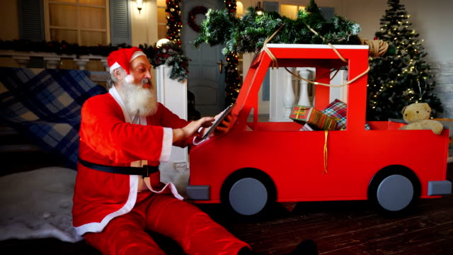 Joyous Santa Claus enjoying with modern gadget video