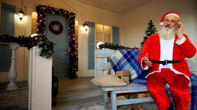 Joyous Santa Claus speaking by phone video