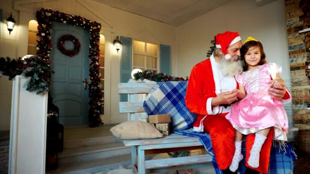 Joyous Santa Claus speaking with little princess video