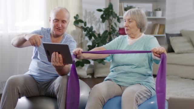 glada senior par använda tablet och utövar hemma - hemmaträning bildbanksvideor och videomaterial från bakom kulisserna