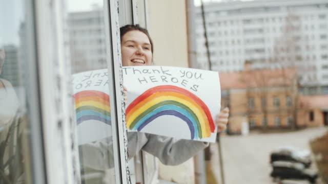 stockvideo's en b-roll-footage met vrolijke vrouw holding «nhs dank u helden» poster en zwaaien uit het raam - bord bericht