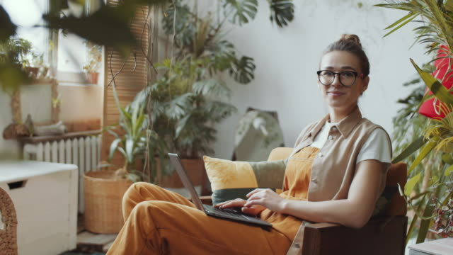 Joyous Woman with Laptop Looking at Camera and Laughing in Home Garden Cheerful Caucasian woman sitting in armchair with laptop on her lap, looking at camera with smile and laughing while working in room with lots of houseplants mid adult women stock videos & royalty-free footage