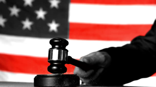 Judge calling order with gavel in american court in selective black and white video