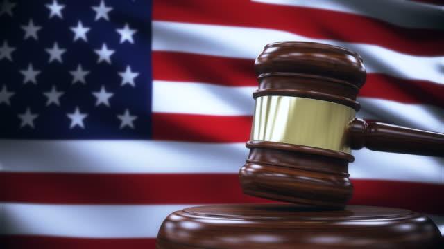 vídeos de stock, filmes e b-roll de martelo de juiz com fundo de bandeira dos estados unidos - domínio