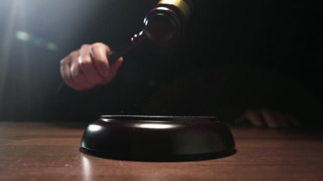 Judge hitting Gavel off a block in courtroom, dark background slow motion dolly shot