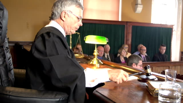 Judge in Court calling order with Jury behind, Courthouse Stock HD video clip footage of a Judge in a Courtroom using his gavel to call order - Crane shot sentencing stock videos & royalty-free footage