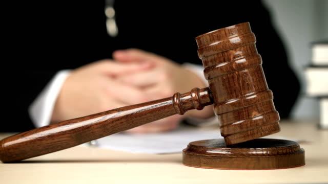 vidéos et rushes de juge assis derrière le bureau dans la salle d'audience, mains jointes. loi, liberté, justice - notaire