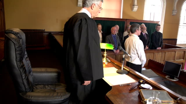 Judge walking into Court, with Jury Standing in Courthouse video