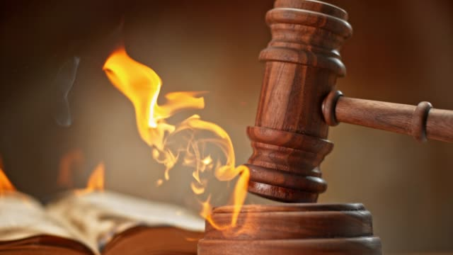 SLO MO LD Judge's gavel striking a burning wooden sound block
