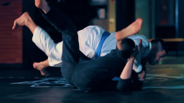 vídeos de stock, filmes e b-roll de os caras do judoca estão brigando no chão, acrobacias excruciantes no parterre. capture com um golpe pelos judocas. - artes marciais