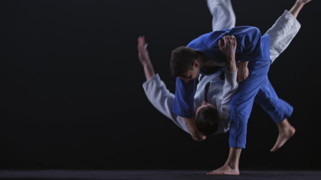 SLO MO LD Judoka in blue outfit grabbing his opponent and throwing him on the floor Slow motion wide locked down shot of a male Judoka in blue outfit grabbing his opponent in white and throwing him on the floor. Shot on black background. Shot in Slovenia. martial arts stock videos & royalty-free footage