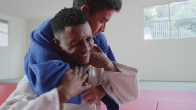 vídeos de stock, filmes e b-roll de judoca estrangula seu oponente no tapete de judô - artes marciais