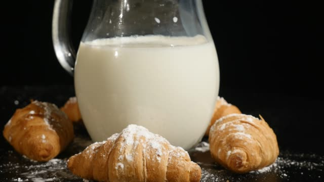 jug of milk with croissant rotate on a black background - декантер стоковые видео и кадры b-roll