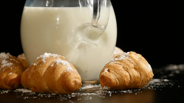 jug of milk with croissant rotate on a black background - decanter video stock e b–roll