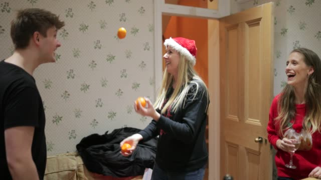 Juggling at Party A woman juggling in the kitchen in the middle of a Christmas party party social event stock videos & royalty-free footage