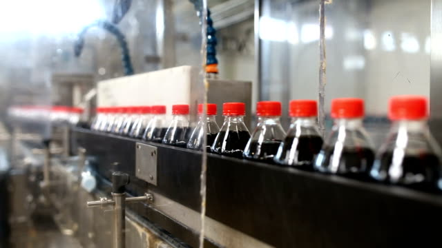 Juice and soda production factory Bottling factory - Black juice or soft drink bottling line for processing and bottling juice into bottles. Selective focus. soda stock videos & royalty-free footage