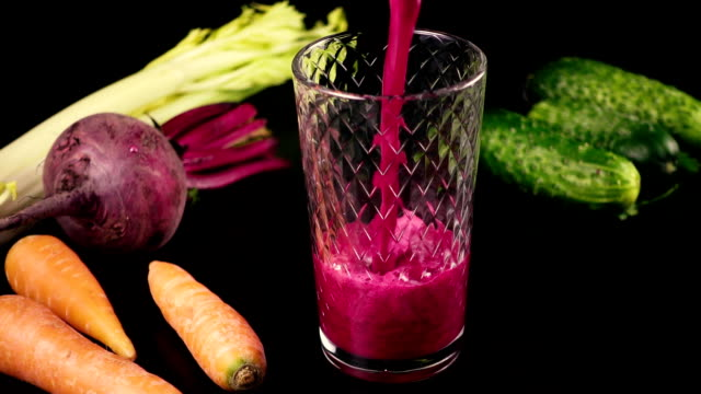 Juice from fresh vegetables, carrots, celery, beets and cucumbers. High speed video