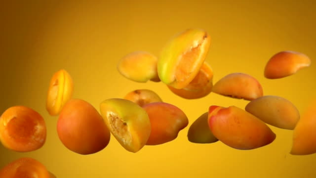Juicy apricot halves bounce on yellow background Delicious juicy apricot halves bounce on a yellow background peach stock videos & royalty-free footage