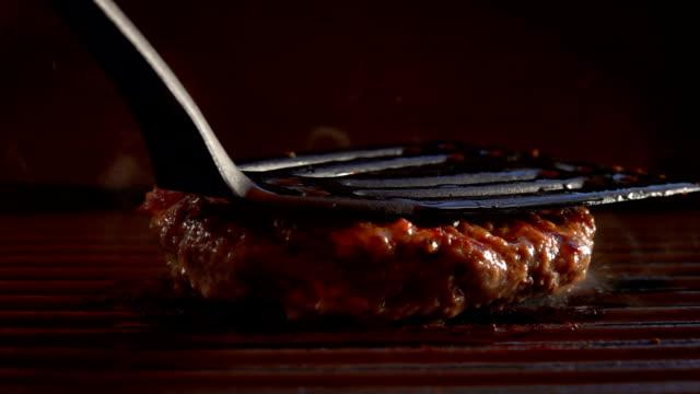saftigt nötkött kotlett för en hamburgare pressas till grillen och brast i lågor - hamburgare bildbanksvideor och videomaterial från bakom kulisserna