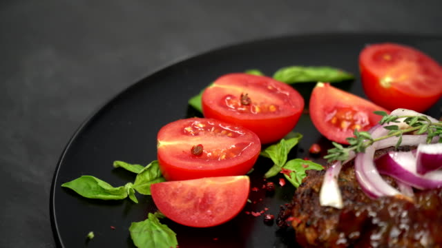 Juicy beef with sauce and onion, side by side sliced sliced tomatoes with basil leaves video