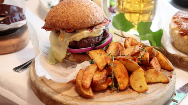Juicy burger with cheese and bacon served with baked potatoes