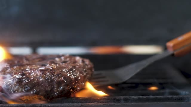 juicy meat for burgers overturned on a hot grill. Slow motion