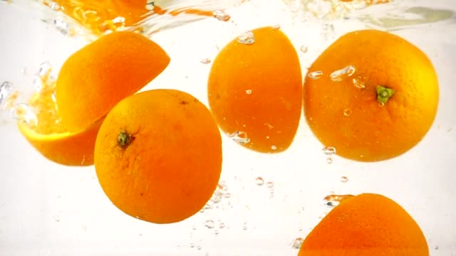 Juicy orange halves are immersed in water, slow motion close-up
