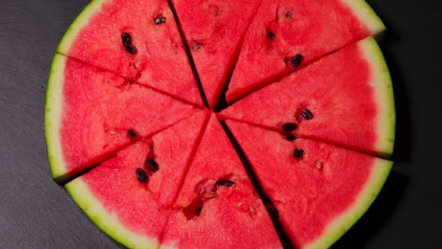 Juicy pieces of watermelon shaped pizza on a black stone table Juicy pieces of watermelon shaped pizza on a black stone table. High quality 4k footage watermelon stock videos & royalty-free footage