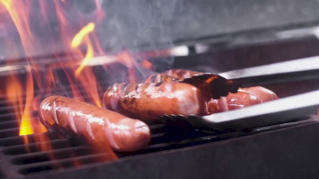 vídeos de stock e filmes b-roll de juicy pork sausages are fried on a hot grill in the fire. turn the tongs. close up. slow motion - jantar assado