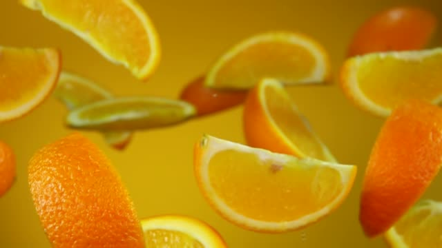 juicy slices of orange are flying up and rotating on the yellow background - healthy green juice video stock e b–roll