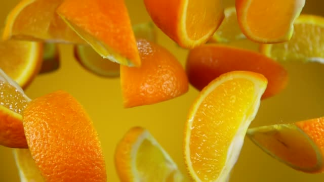Juicy slices of ripe orange are flying up and down on the yellow background - video