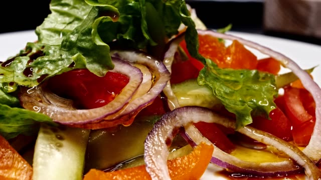 Juicy steak is fried on a barbecue with vegetables and pepper, as well as basil. Fresh rolls and a salad with vegetables and fruits are prepared. 4K video