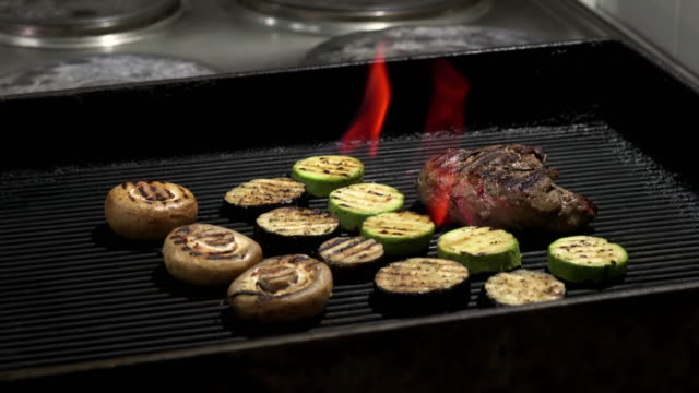 Juicy steaks sizzle on flaming and smoking grill video