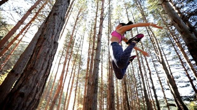 vidéos et rushes de exercice de saut en forêt - vue en contre plongée