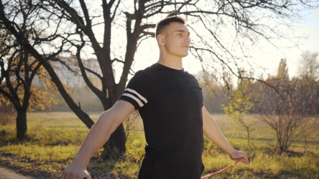 vídeos de stock e filmes b-roll de jump rope workout of a handsome caucasian boy in the autumn park on sunset. young man in sportswear training outdoors. healthy lifestyle, sport concept. - campeão desportivo