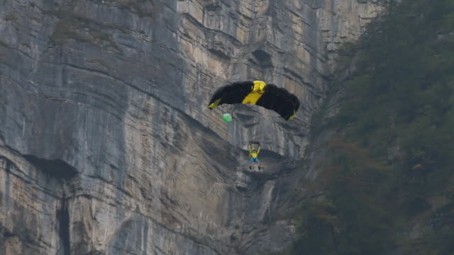 BASE jumper flies with canopy in mountains He passes vertical cliff on descent cliff jumping stock videos & royalty-free footage